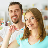 Happy couple with toothbrushes about to brush their teeth.